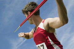 Athlete About To Throw Javelin. Young male athlete about to throw javelin against the sky Royalty Free Stock Photo
