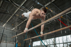 Athlete topless doing exercises on the uneven bars Stock Image