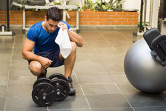Athlete Toweling Brow. Male athlete kneeling down by dumbbells toweling sweat of his brow Stock Images