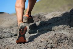 Athlete trail running in the mountains on rocky terrain. Sports shoes detail Stock Image