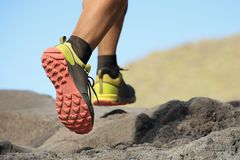 Athlete trail running in the mountains on rocky terrain. Sports shoes detail Royalty Free Stock Images