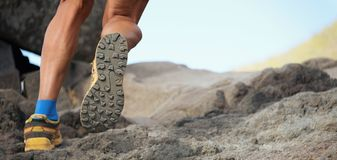 Athlete trail running in the mountains on rocky terrain. Sports shoes detail Royalty Free Stock Photography