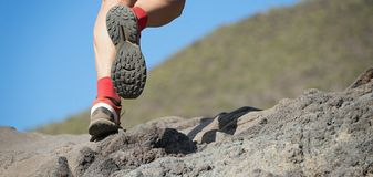 Athlete trail running in the mountains on rocky terrain. Sports shoes detail Royalty Free Stock Image