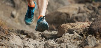 Athlete trail running in the mountains on rocky terrain. Sports shoes detail Stock Photography