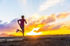 Trail running woman runner on sunset road. Athlete trail running silhouette of a female runner on sunset road sunrise. Cardio fitness woman training for marathon stock photo