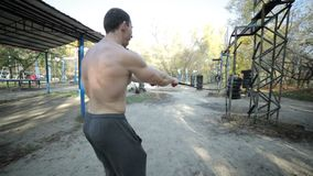 Athlete trains his muscles. Athletes train the muscles engaged in a sports park, he makes dynamic exercises stock footage