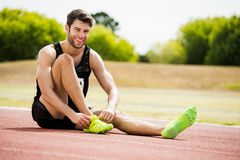 Athlete tying his shoe laces on running track. On a sunny day Royalty Free Stock Photos
