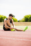 Athlete tying his shoe laces on running track. On a sunny day Stock Photo