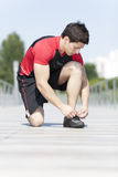 Athlete tying the laces of his shoes Stock Photos