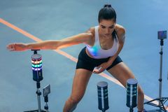 Athlete using visual stimulus system at sports lab. Sportswoman exercising with lights around, reaction training session at gym. Female athlete using a visual Stock Photo
