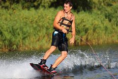 Athlete on the wakeboard. Athlete enjoys skateboarding on the river and looking away royalty free stock photo