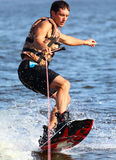 Athlete on the wakeboard. Athlete enjoys skateboarding on the river and looking away stock photo