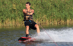 Athlete on the wakeboard. Athlete enjoys wakeboarding on the river and looking away stock image
