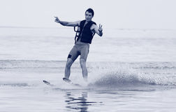 Athlete waterskiing. Rides on the water with hands-free royalty free stock photography