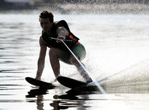 Athlete waterskiing. Athlete touches the water when riding on water skis royalty free stock images