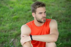 Athlete wear pedometer bracelet on hand. Athletic man relax on green grass. Checking workout results. Technologies make Royalty Free Stock Images