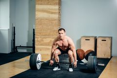 Athlete wearing black shorts lifting big barbell. Muscular fitness man doing deadlift a barbell in modern fitness center.Functional training.Snatch exercise Stock Photos