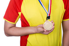 Athlete wearing generic gold medal with ribbon on his neck Stock Photography