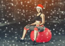 An athlete wearing a Santa Claus hat is doing sports with a yogaball. royalty free stock photo