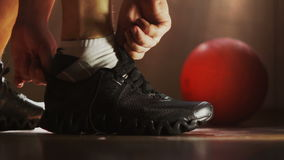 The athlete wears sneakers and tying shoelaces. The athlete wears sneakers in the locker room and tying shoelaces. Gym, basketball stock video