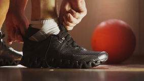 The athlete wears sneakers and tying shoelaces. The athlete wears sneakers in the locker room and tying shoelaces. Gym, basketball stock video footage