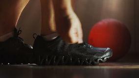 The athlete wears sneakers and tying shoelaces. The athlete wears sneakers in the locker room and tying shoelaces. Gym, basketball stock footage