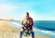 Athlete with weight on sandy beach. Muscular male athlete exercise with weight on sandy beach, blue sky and sea on background. Fitness training with weight Royalty Free Stock Photography