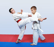 An athlete with a white belt beat a punch in response to kick an athlete with a red belt Stock Image