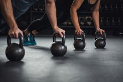 Cross fit training with kettleballs. Athlete woman doing push ups on two kettlebells Royalty Free Stock Photography
