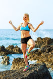 Athlete woman doing sport exercising on the rocks by the sea Stock Photo