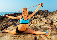 Athlete woman doing sport exercising with the rope on the rocks Royalty Free Stock Photography
