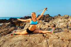 Athlete woman doing sport exercising with the rope on the rocks Royalty Free Stock Images