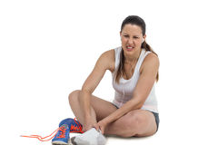 Athlete woman with foot pain on white background royalty free stock photography