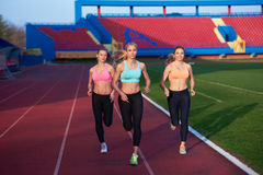 Athlete woman group  running on athletics race track Stock Image