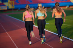 Athlete woman group running on athletics race track. Athlete women group running on athletics race track on soccer stadium and representing competition and royalty free stock photos