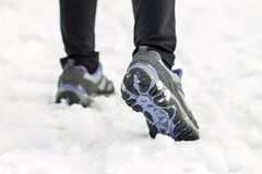 Athlete woman jogging feet on snow at morning training. Sport background Royalty Free Stock Images