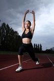 Athlete woman lunge stretch on athletics track Stock Photography