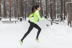 Athlete woman runner running in cold snowing weather. Cardio street training marathon jogging. Stock Photo