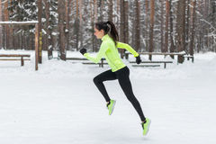 Athlete woman runner running in cold snowing weather. Cardio street training marathon jogging. Royalty Free Stock Photo