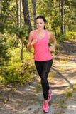 Athlete woman running through forest training stock photos