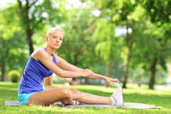 Athlete woman sitting on an excercising mat and stretching Stock Images