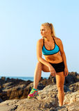 Athlete woman standing after sport exercising on the rocks by th Royalty Free Stock Photos