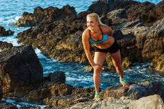 Athlete woman standing after sport exercising on the rocks by th Royalty Free Stock Image