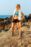 Athlete woman standing after sport exercising on the rocks by th Royalty Free Stock Photo