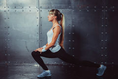 Athlete woman stretching legs in gym doing fitness Stock Photo
