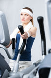 Athlete woman training on simulators in gym Royalty Free Stock Images