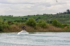 Athlete Woman is Wakeboarding at the Cable Park stock images