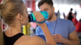 Athlete woman drinking water and listening to coach advice after workout in gym stock photo