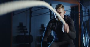 Athlete working out with heavy ropes in gym. Close view of frowning sportive man wriggling long heavy ropes working out and training endurance in dark gym. Slow stock video footage