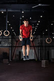 Athlete working out his muscles on rings Royalty Free Stock Image